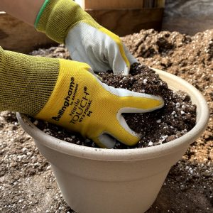 close up of hand with yellow gloves working on a pot